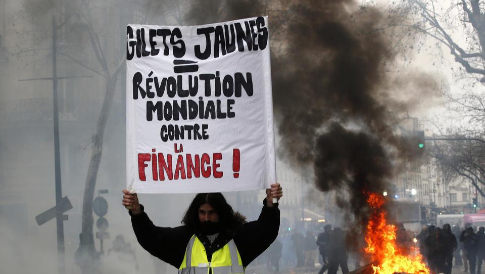 26.01.2019, Frankreich, Paris: Ein Demonstrant hält ein Schild mit der Aufschrift «Gelbwesten = weltweite Revolution gegen die Finanzwirtschaft». In der französischen Hauptstadt kam es zu erneuten «Gelbwesten»-Protesten. Die Aktionen richten sich gegen di